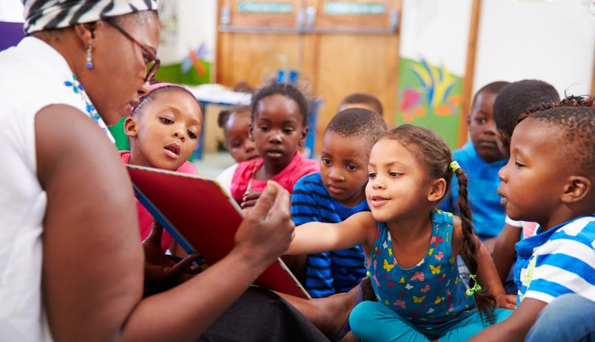 Young children crowding around a teacher holding open a book.