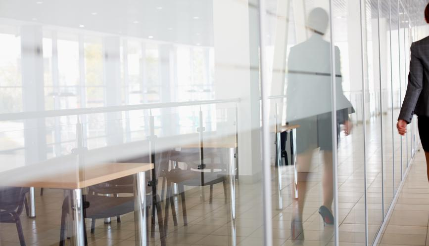 Reflection of woman wearing business attire on the window of a conference room.