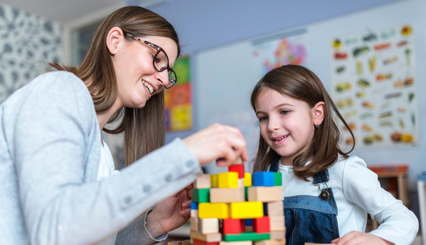 Woman and young girl playing with building blocks.
