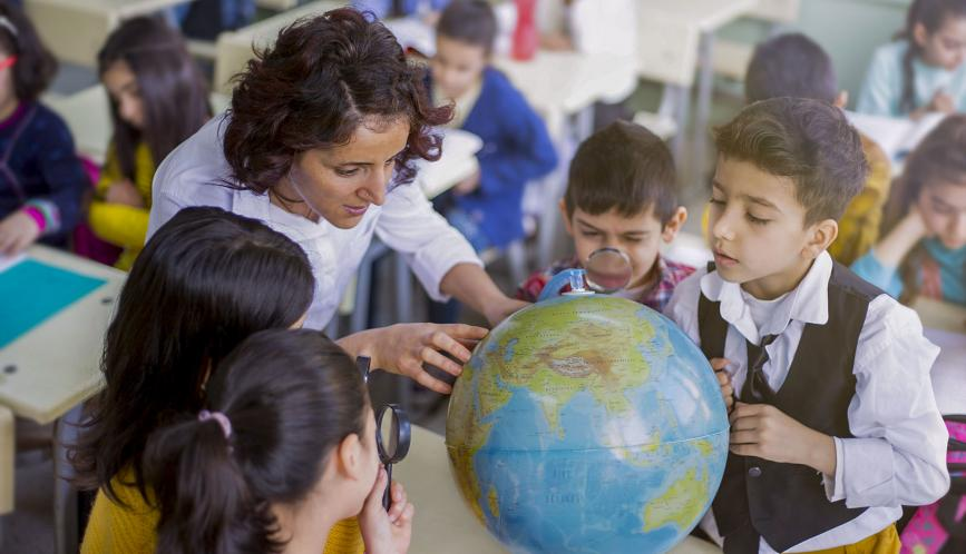 School children and teacher looking at a globe in a classroom.