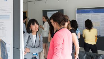 Students in discussion during a summer school poster session.