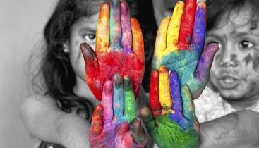 A stock image of two children in black and white, with their hands outstretched and covered in multicolored paint.