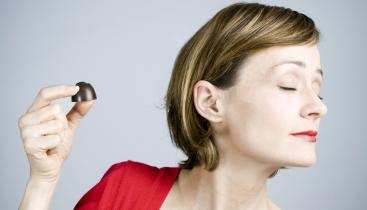 A stock image of a woman holding up a chocolate, but her face is turned away from it.