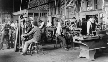 A historic, black and white image of a shop class at work at different machines.