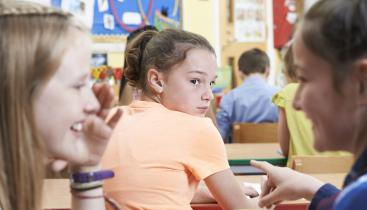 Girl look back at two girls talking, in a classroom