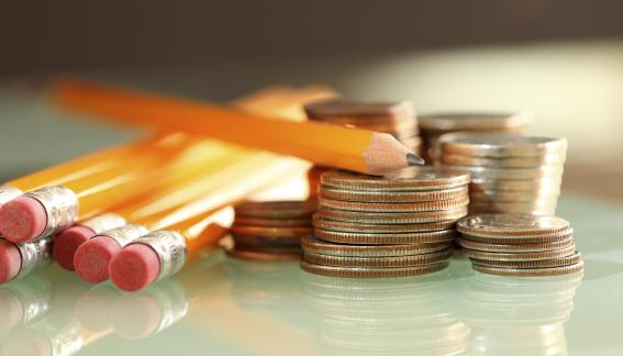 A stock image of pencils sitting beside small stacks of quarters and other change.