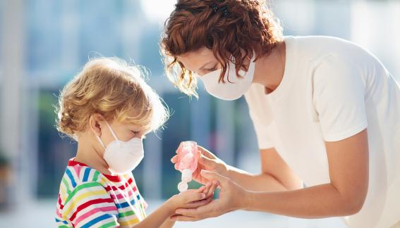 Adult giving a young child hand sanitizer, both are wearing masks.
