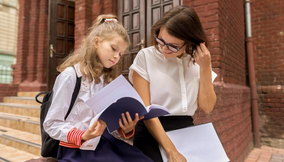 Student and adult reading a notebook.